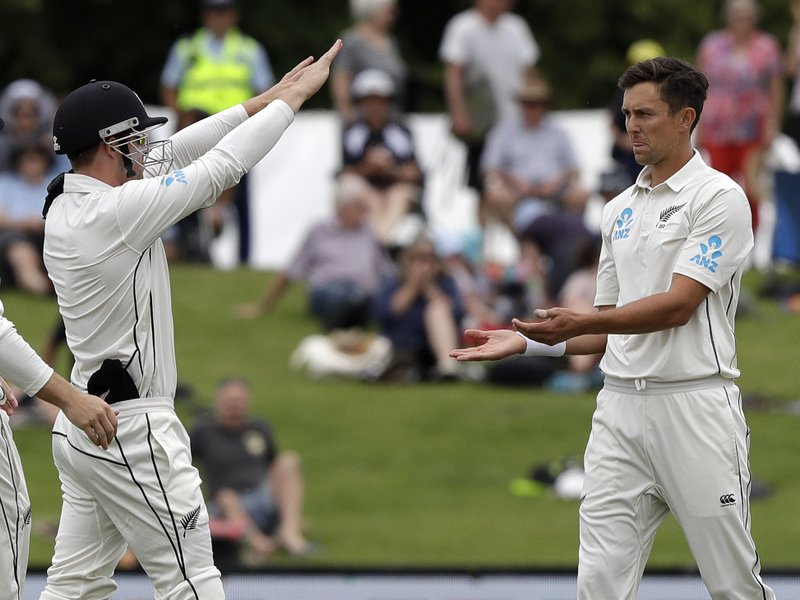 New Zealand's Henry Nicholls, left, congratulates bowler Trent Boult after the dismissal Sri Lanka's Dushmantha Chameera during play on the final day of the second cricket test between New Zealand and Sri Lanka at Hagley Oval in Christchurch, New Zealand, Sunday, Dec. (AP Photo/Mark Baker)