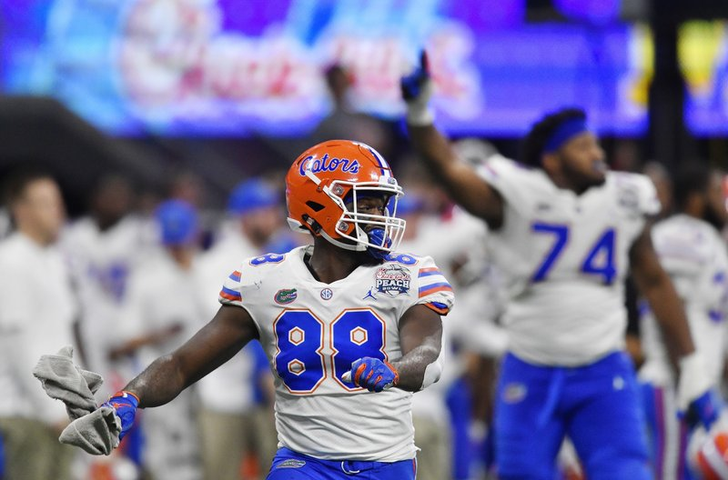 Florida tight end Kemore Gamble (88) and Florida offensive lineman Fred Johnson (74) celebrate after the Peach Bowl NCAA college football game against Michigan, Saturday, Dec. (AP Photo/Mike Stewart)