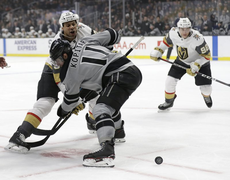 Vegas Golden Knights' Ryan Reaves, left, faces off against Los Angeles Kings' Anze Kopitar during the first period of an NHL hockey game Saturday, Dec. (AP Photo/Marcio Jose Sanchez)