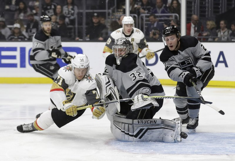 Los Angeles Kings goaltender Jonathan Quick, center, deflects a shot in front of Vegas Golden Knights' William Karlsson, left, during the first period of an NHL hockey game Saturday, Dec. (AP Photo/Marcio Jose Sanchez)