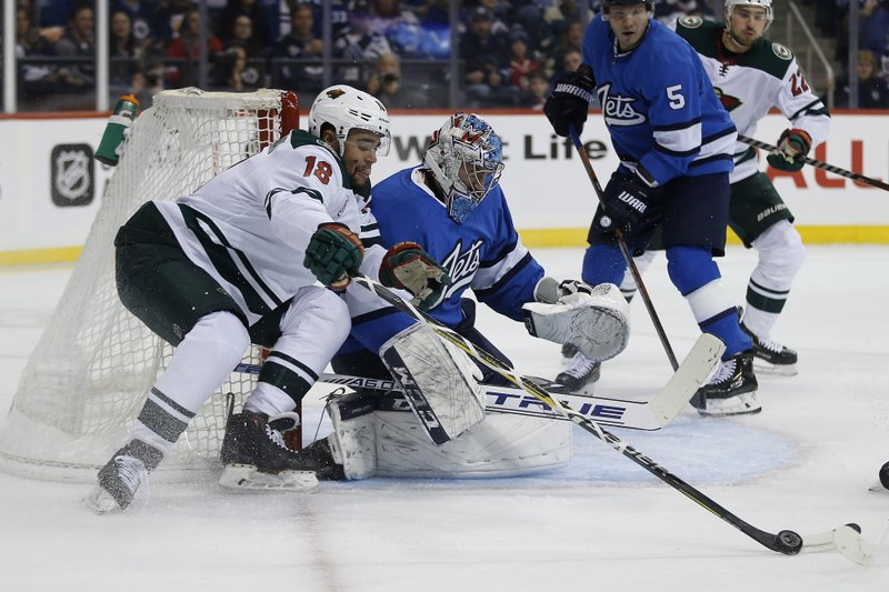 Minnesota Wild's Jordan Greenway (18) tries to recover the rebound off his shot on Winnipeg Jets goaltender Connor Hellebuyck (37) during first period NHL action in Winnipeg, Manitoba, on Saturday, Dec. (John Woods/The Canadian Press via AP)