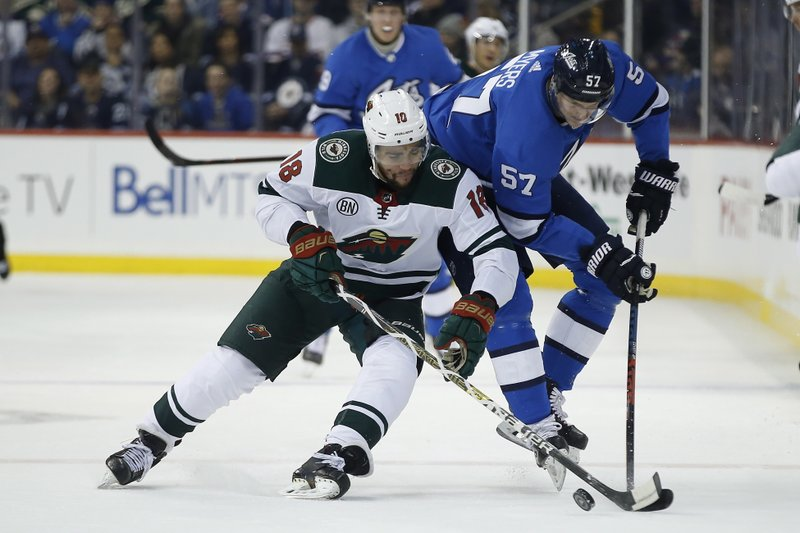 Minnesota Wild's Jordan Greenway (18) steals the puck from Winnipeg Jets' Tyler Myers (57) during first period NHL action in Winnipeg, Manitoba, on Saturday, Dec. (John Woods/The Canadian Press via AP)