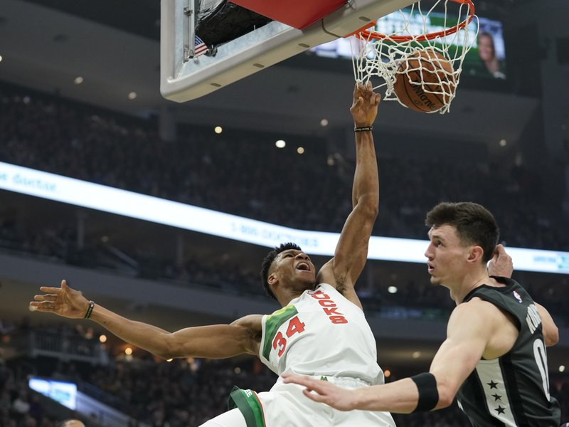 Milwaukee Bucks' Giannis Antetokounmpo dunks over Brooklyn Nets' Rodions Kurucs during the first half of an NBA basketball game Saturday, Dec. (AP Photo/Morry Gash)