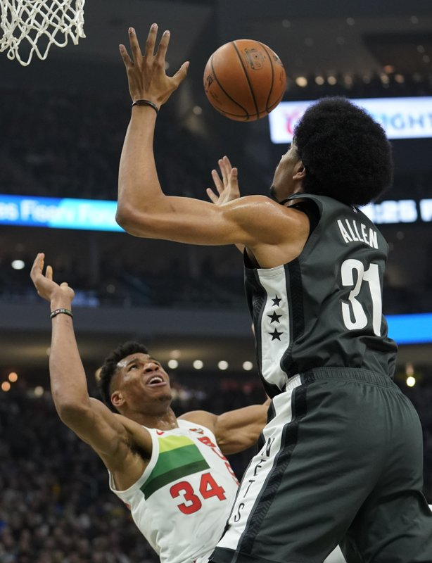 Brooklyn Nets' Jarrett Allen blocks a shot by Milwaukee Bucks' Giannis Antetokounmpo during the first half of an NBA basketball game Saturday, Dec. (AP Photo/Morry Gash)