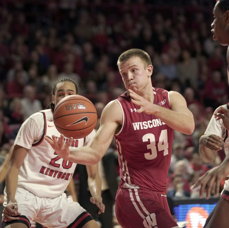 Wisconsin guard Brad Davison (34) tries to hold on to the ball as Western Kentucky guard Dalano Banton (20) defends during the first half of an NCAA college basketball game Saturday, Dec. (AP Photo/Tim Broekema)