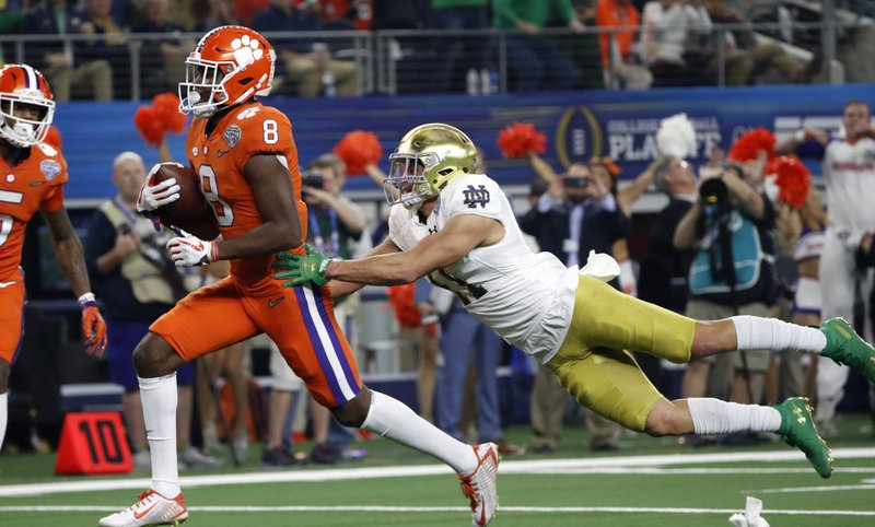 Clemson wide receiver Justyn Ross (8) escapes a tackle attempt by Notre Dame safety Alohi Gilman, right, as Ross reaches the end zone for a touchdown in the first half of the NCAA Cotton Bowl semi-final playoff football game, Saturday, Dec. (AP Photo/Roger Steinman)