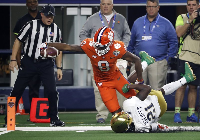 Clemson wide receiver Justyn Ross (8) leans forward and reaches the end zone for a touchdown after getting past Notre Dame safety Jalen Elliott (21) in the first half of the NCAA Cotton Bowl semi-final playoff football game, Saturday, Dec. (AP Photo/Roger Steinman)