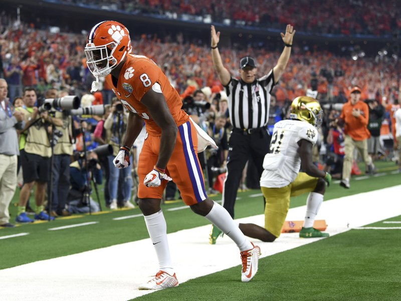 Clemson wide receiver Justyn Ross (8) celebrates his touchdown catch in front of Notre Dame safety Jalen Elliott (21) in the first half of the NCAA Cotton Bowl semi-final playoff football game, Saturday, Dec. (AP Photo/Jeffrey McWhorter)
