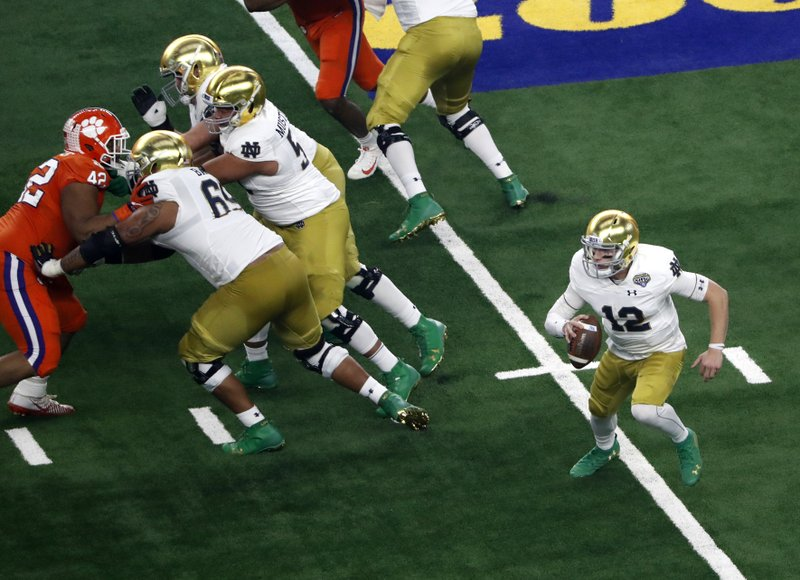 Notre Dame quarterback Ian Book (12) scrambles out of the pocket for a gain in the first half of the NCAA Cotton Bowl semi-final playoff football game against Clemson on Saturday, Dec. (AP Photo/Roger Steinman)
