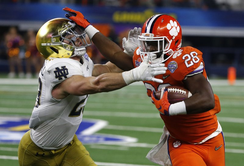 Notre Dame linebacker Drue Tranquill (23) attempts to stop Clemson running back Tavien Feaster (28) from gaining extra yardage on a running play in the second half of the NCAA Cotton Bowl semi-final playoff football game, Saturday, Dec. (AP Photo/Michael Ainsworth)