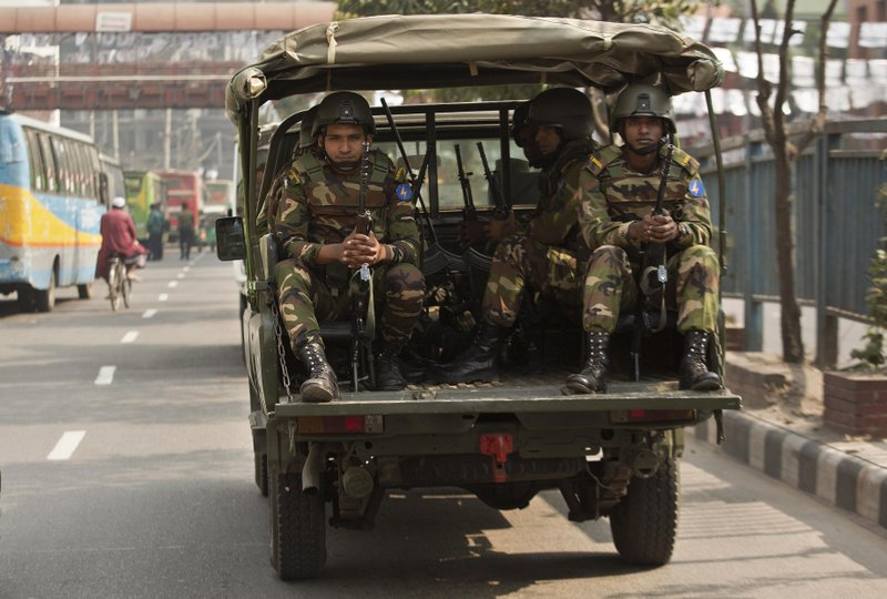 Bangladeshi army soldiers sit inside a vehicle as they patrol the streets on the eve of the general elections in Dhaka, Bangladesh, Saturday, Dec. (AP Photo/Anupam Nath)