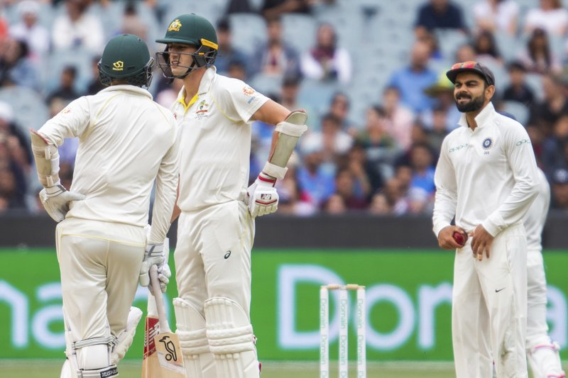 Australia's Nathan Lyon, left, and Pat Cummins, center, at the end of an over speak as India's Virat Kohli looks on during play on day five of the third cricket test between India and Australia in Melbourne, Australia, Sunday, Dec. (AP Photo/Asanka Brendon Ratnayake)