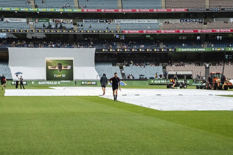 Melbourne cricket ground curating staff place pegs into the rain covers as the start of play is delayed during day five of the third cricket test between India and Australia in Melbourne, Australia, Sunday, Dec. (AP Photo/Asanka Brendon Ratnayake)