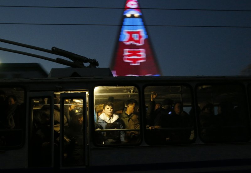 In this Dec. 20, 2018 photo, people ride on a tram as a propaganda message is partially seen displayed on the facade of the pyramid-shaped Ryugyong Hotel in Pyongyang, North Korea. (AP Photo/Dita Alangkara)
