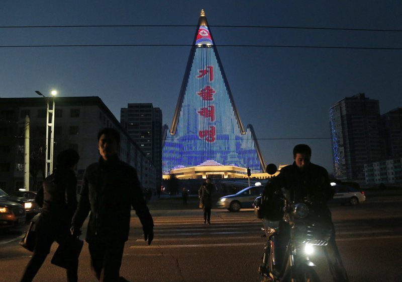 In this  Dec. 20, 2018 photo, people cross the street as a propaganda message is displayed on the facade of the pyramid-shaped Ryugyong Hotel in Pyongyang, North Korea. (AP Photo/Dita Alangkara)