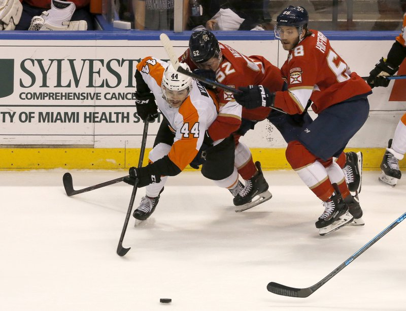 Philadelphia Flyers center Phil Varone skates to the puck as Florida Panthers defenseman MacKenzie Weegar (52) and left wing Mike Hoffman (68) pursue in the second period of an NHL hockey game, Saturday Dec. (AP Photo/Joe Skipper)