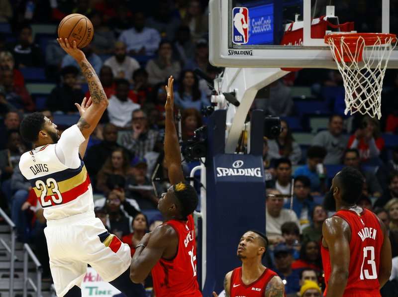 New Orleans Pelicans forward Anthony Davis (23) puts up a shot over Houston Rockets center Clint Capela (15) during the first half of an NBA basketball game, Saturday, Dec. (AP Photo/Butch Dill)