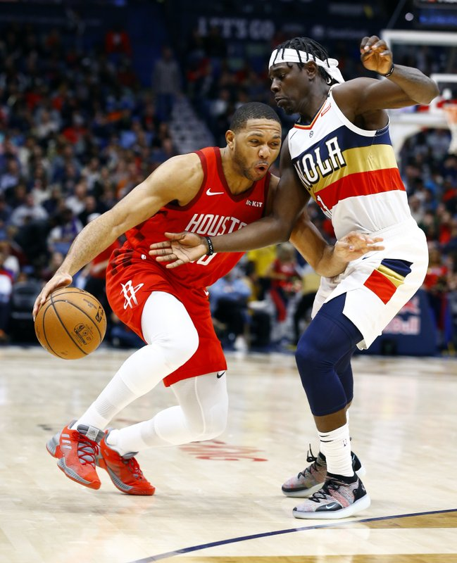 Houston Rockets guard Eric Gordon (10) drives to the basket around New Orleans Pelicans guard Jrue Holiday (11) during the first half of an NBA basketball game, Saturday, Dec. (AP Photo/Butch Dill)