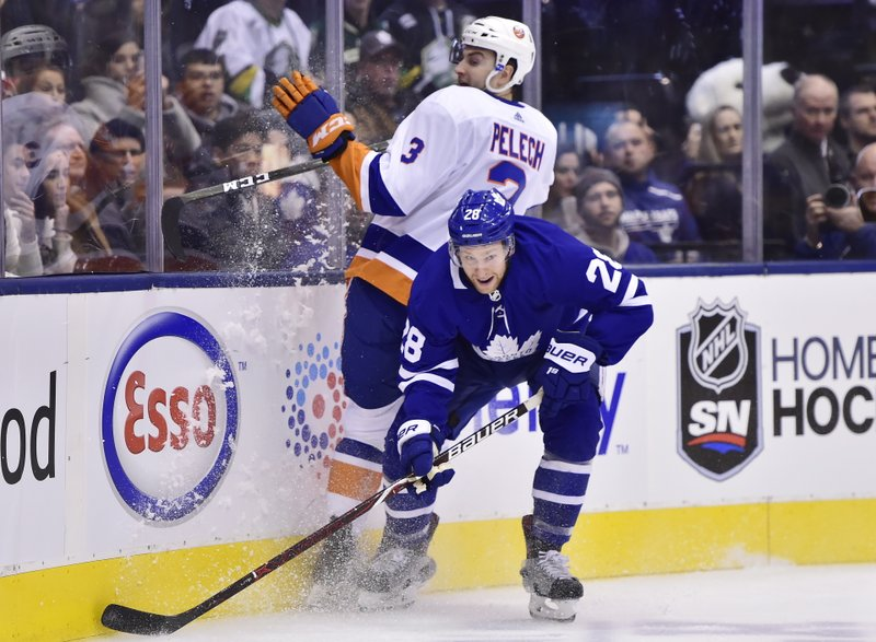 Toronto Maple Leafs right wing Connor Brown (28) collides with New York Islanders defenseman Adam Pelech (3) during the first period of an NHL hockey game Saturday, Dec. (Frank Gunn/The Canadian Press via AP)