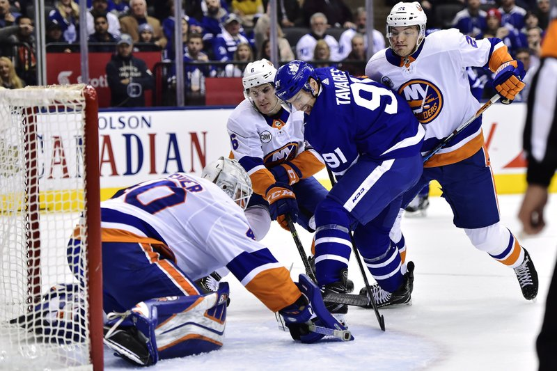Toronto Maple Leafs center John Tavares (91) battles for the puck in front of New York Islanders goaltender Robin Lehner (40) as Islanders defensemen Ryan Pulock (6) and Scott Mayfield (24) defend during the first period of an NHL hockey game Saturday, Dec. (Frank Gunn/The Canadian Press via AP)