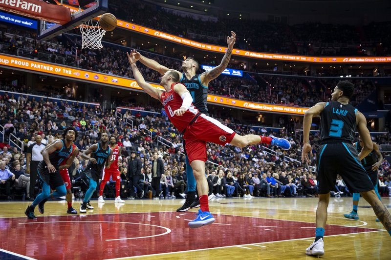 Washington Wizards forward Sam Dekker (8) attempts a layup past Charlotte Hornets center Willy Hernangomez (41) and guard Jeremy Lamb (3) during the second half of an NBA basketball game Saturday, Dec. (AP Photo/Al Drago)
