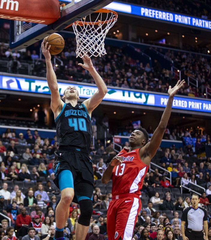 Charlotte Hornets center Cody Zeller (40) makes a layup past Washington Wizards center Thomas Bryant (13) during the first half of an NBA basketball game Saturday, Dec. (AP Photo/Al Drago)