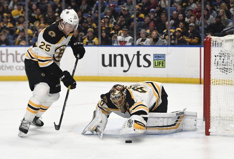 Boston Bruins goalie Tuukka Rask, right, reaches for a loose puck as the play is covered by defenseman Brandon Carlo (25) during the second period of an NHL hockey game against the Buffalo Sabres in Buffalo, N. (AP Photo/Adrian Kraus)