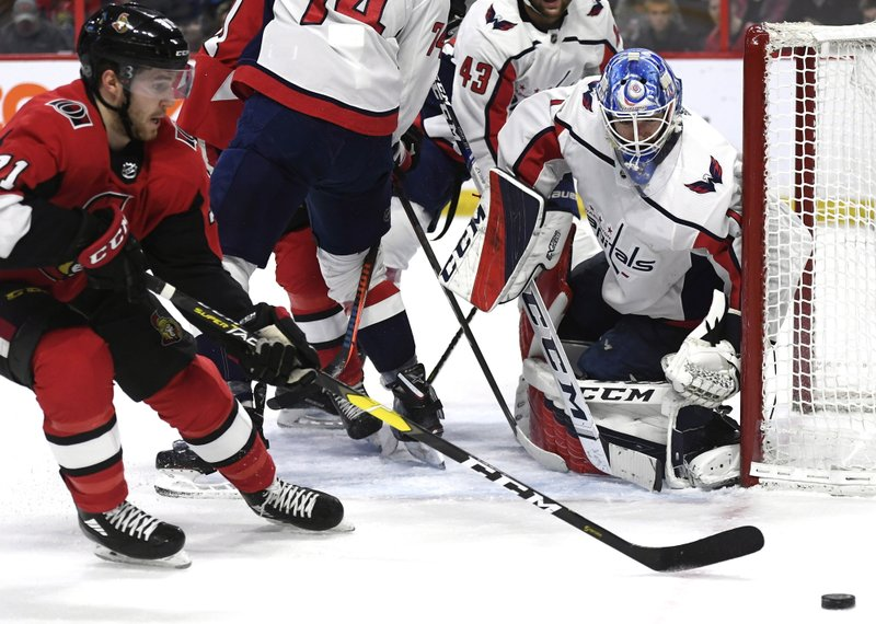 Washington Capitals goaltender Pheonix Copley (1) watches the puck as Ottawa Senators center Chris Tierney (71) tries to control it during the second period of an NHL hockey game, Saturday, Dec. (Justin Tang/The Canadian Press via AP)