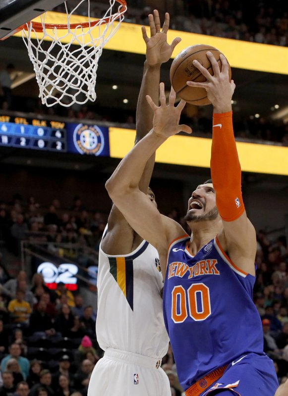 New York Knicks' Enes Kanter (00) attempts a layup as Utah Jazz's Derrick Favors, left, defends in the first half of an NBA basketball game on Saturday, Dec. (AP Photo/Kim Raff)