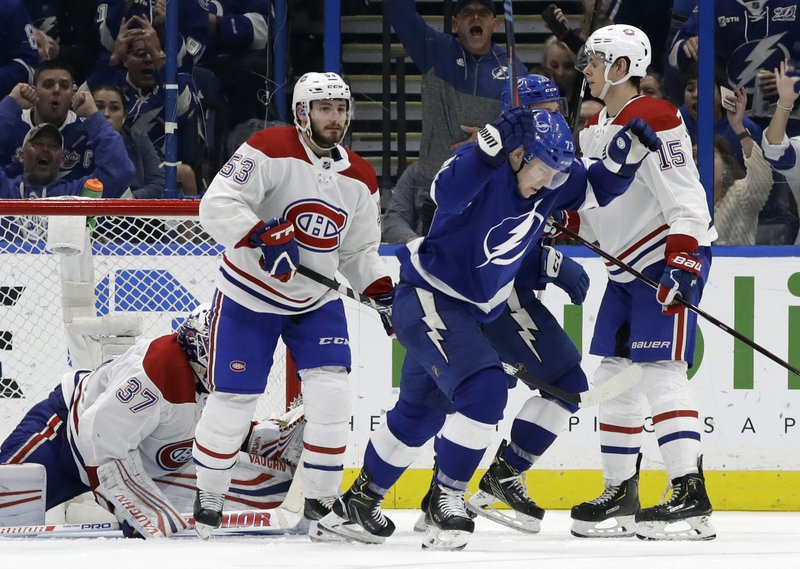 Tampa Bay Lightning left wing Adam Erne (73) celebrates in front of Montreal Canadiens defenseman Victor Mete (53) and center Jesperi Kotkaniemi (15) after scoring during the third period of an NHL hockey game Saturday, Dec. (AP Photo/Chris O'Meara)
