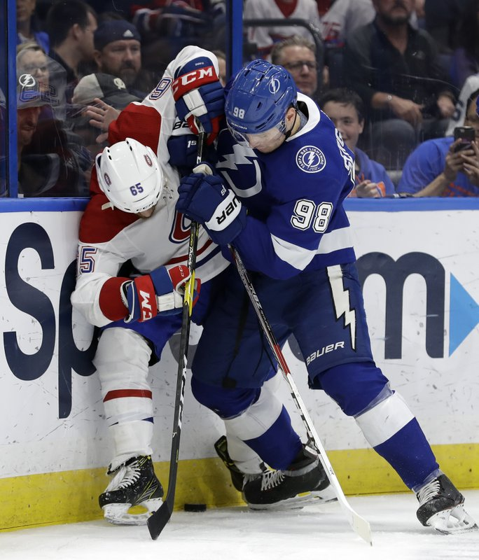 Tampa Bay Lightning defenseman Mikhail Sergachev (98) pins Montreal Canadiens right wing Andrew Shaw (65) to the dasher during the first period of an NHL hockey game Saturday, Dec. (AP Photo/Chris O'Meara)