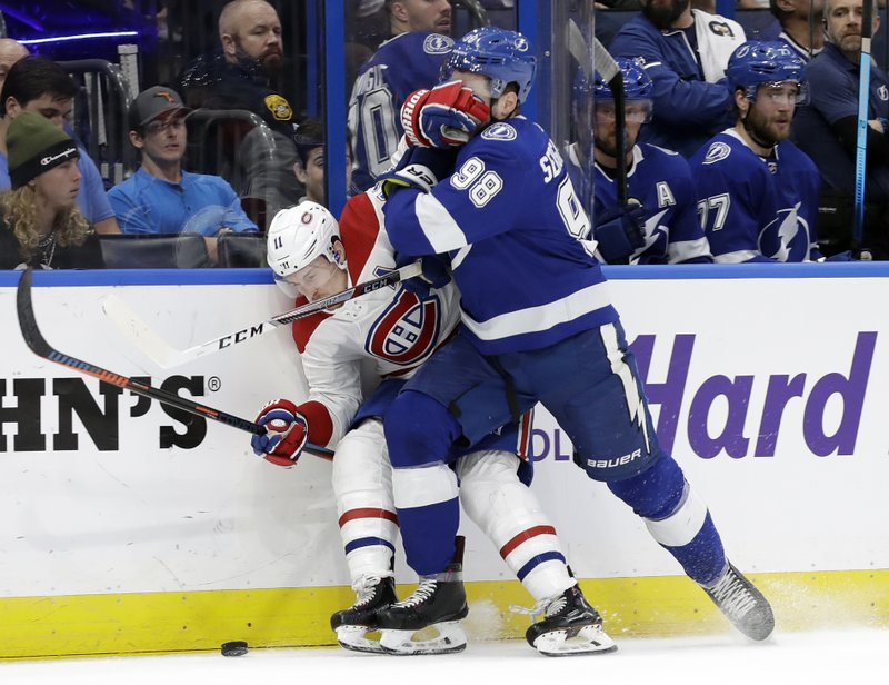 Montreal Canadiens right wing Brendan Gallagher (11) and Tampa Bay Lightning defenseman Mikhail Sergachev (98) battle for the puck during the first period of an NHL hockey game Saturday, Dec. (AP Photo/Chris O'Meara)