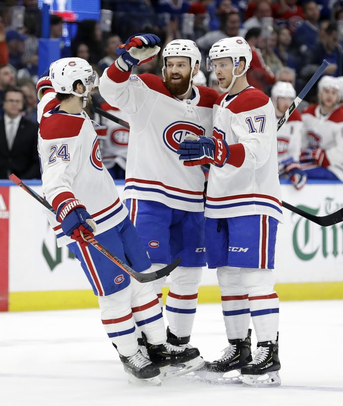 Montreal Canadiens defenseman Jordie Benn (8) celebrates his goal against the Tampa Bay Lightning with center Phillip Danault (24) and defenseman Brett Kulak (17) during the first period of an NHL hockey game Saturday, Dec. (AP Photo/Chris O'Meara)
