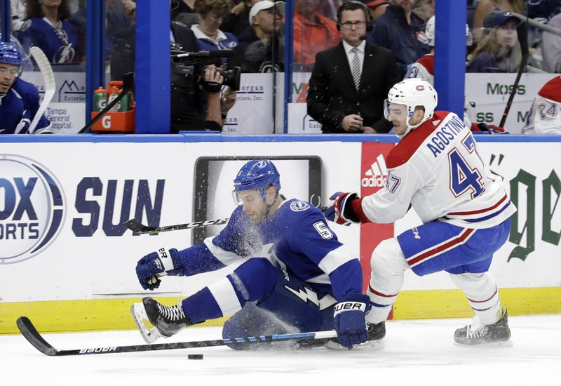 Montreal Canadiens left wing Kenny Agostino (47) takes down Tampa Bay Lightning defenseman Dan Girardi (5) as they chase the puck during the first period of an NHL hockey game Saturday, Dec. (AP Photo/Chris O'Meara)