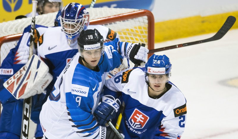Slovakia's Milos Roman (26) tries to clear Finland's Rasmus Kupari (19) from in front of Slovakia goaltender Samuel Hlavaj (2) during the second period of a world junior hockey championships game in Victoria, British Columbia, Saturday, Dec. (Jonathan Hayward/The Canadian Press via AP)