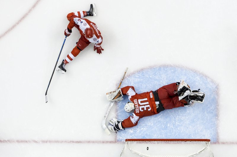 Denmark goalie Mads Soegaard (30) lies on the ice after allowing a goal to Switzerland's Philipp Kurashev (not shown) as Switzerland's Marco Lehmann (6) looks on during first-period IIHF world junior hockey championship game action in Vancouver, British Columbia, Saturday, Dec. (Darryl Dyck/The Canadian Press via AP)