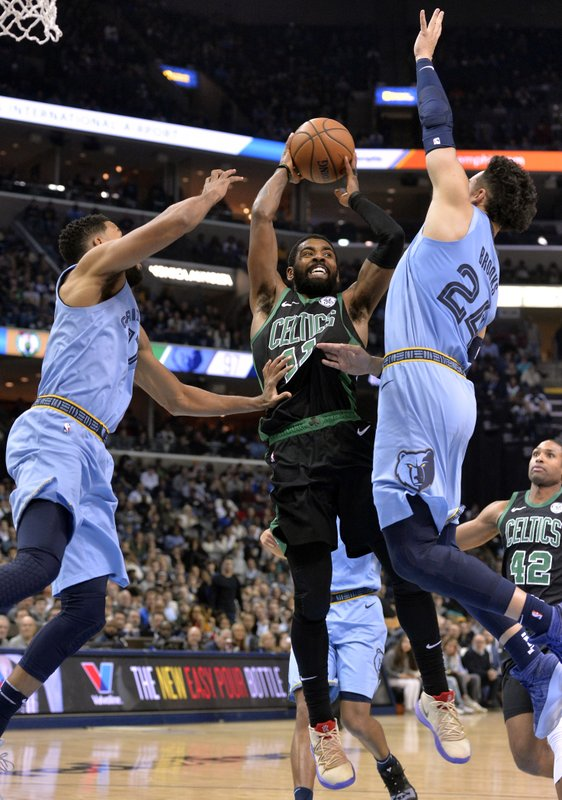 Boston Celtics guard Kyrie Irving (11) controls the ball between Memphis Grizzlies guards Garrett Temple (17) and Dillon Brooks (24) during the second half of an NBA basketball game Saturday, Dec. (AP Photo/Brandon Dill)
