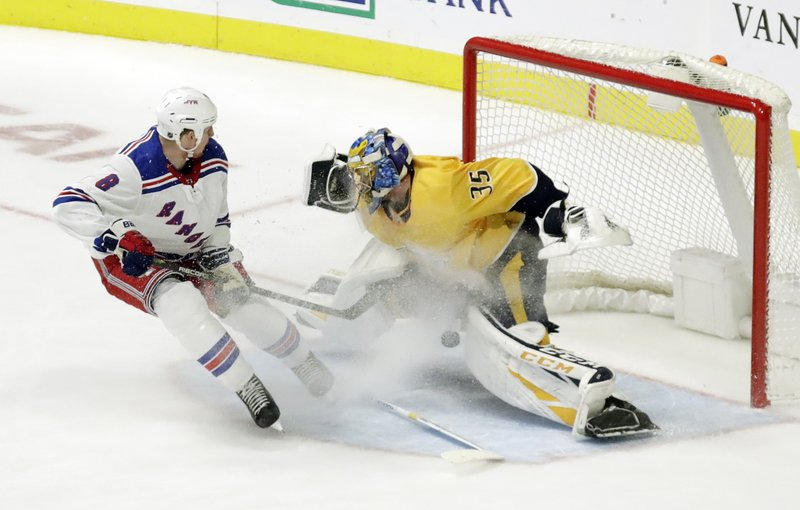 Nashville Predators goaltender Pekka Rinne (35), of Finland, stops a shot as New York Rangers left wing Cody McLeod (8) closes in during the second period of an NHL hockey game Saturday, Dec. (AP Photo/Mark Humphrey)