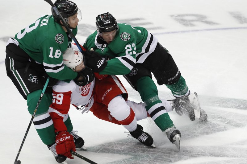 Detroit Red Wings left wing Tyler Bertuzzi (59) is squeezed by Dallas Stars center Tyler Pitlick (18) and defenseman Esa Lindell (23) during the first period of an NHL hockey game in Dallas, Saturday, Dec. (AP Photo/LM Otero)