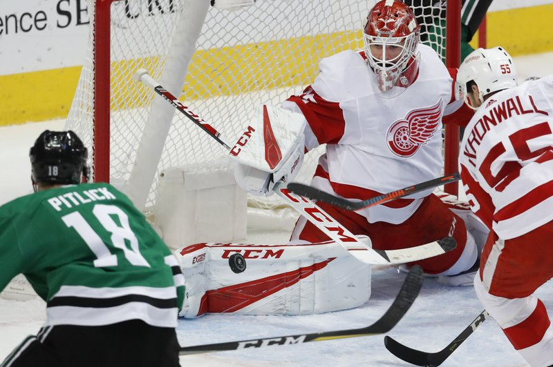 Detroit Red Wings goaltender Jonathan Bernier (45) blocks a shot as defenseman Niklas Kronwall (55) and Dallas Stars center Tyler Pitlick (18) look on during the first period of an NHL hockey game in Dallas, Saturday, Dec. (AP Photo/LM Otero)