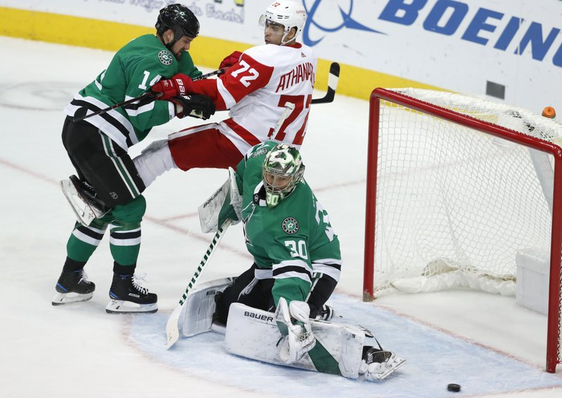 Detroit Red Wings center Andreas Athanasiou (72) is tied up by Dallas Stars left wing Jamie Benn (14) as goaltender Ben Bishop (30) reaches for a shot on goal during the first period of an NHL hockey game in Dallas, Saturday, Dec. (AP Photo/LM Otero)