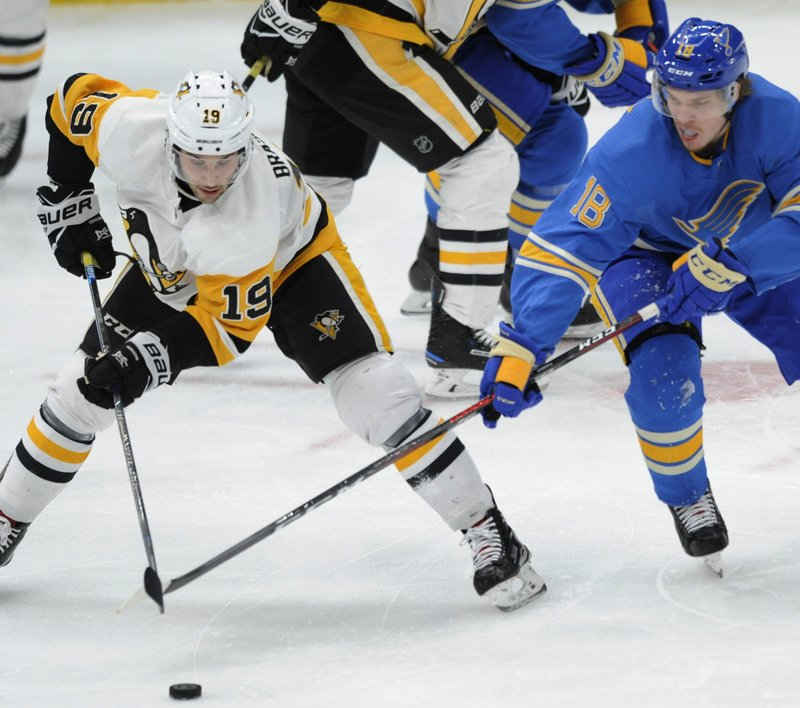 Pittsburgh Penguins' Derick Brassard (19) and St. Louis Blues' Robert Thomas (18) reach for the puck during the third period of an NHL hockey game Saturday, Dec. (AP Photo/Bill Boyce)