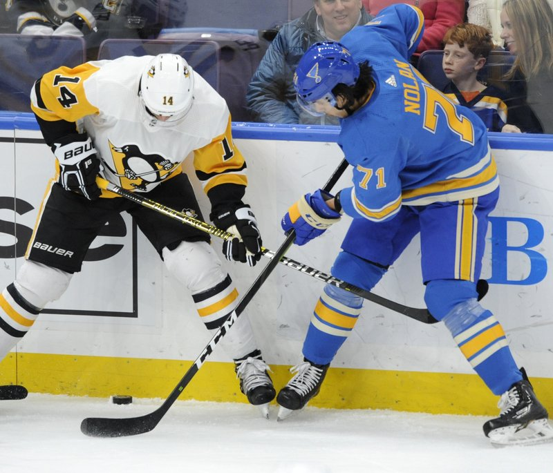 St. Louis Blues' Jordan Nolan (71) reaches for the puck with Pittsburgh Penguins' Tanner Pearson (14) during the first period of an NHL hockey game, Saturday, Dec. (AP Photo/Bill Boyce)