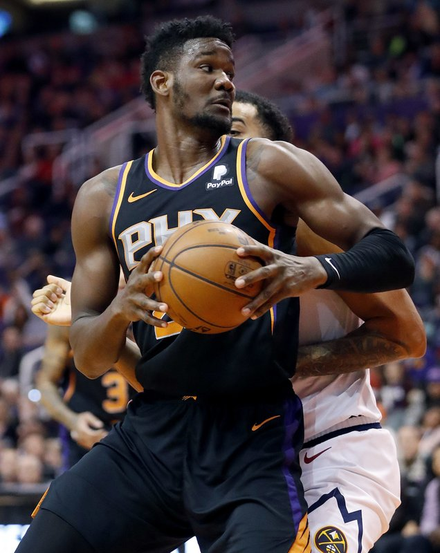 Phoenix Suns center Deandre Ayton (22) backs against the Denver Nuggets during the second half of an NBA basketball game, Saturday, Dec. (AP Photo/Matt York)