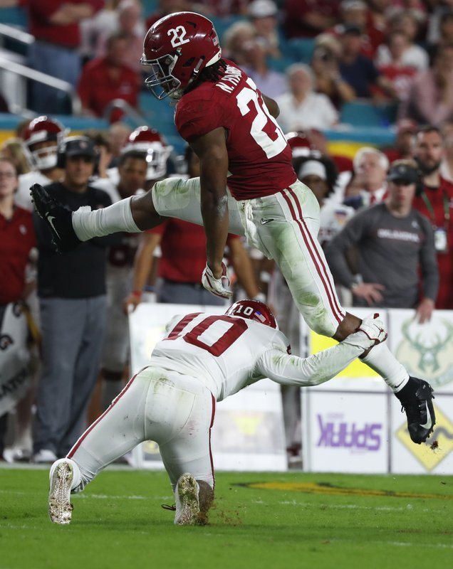 Alabama running back Najee Harris (22) jumps over Oklahoma safety Patrick Fields (10), during the first half of the Orange Bowl NCAA college football game, Saturday, Dec. (AP Photo/Wilfredo Lee)