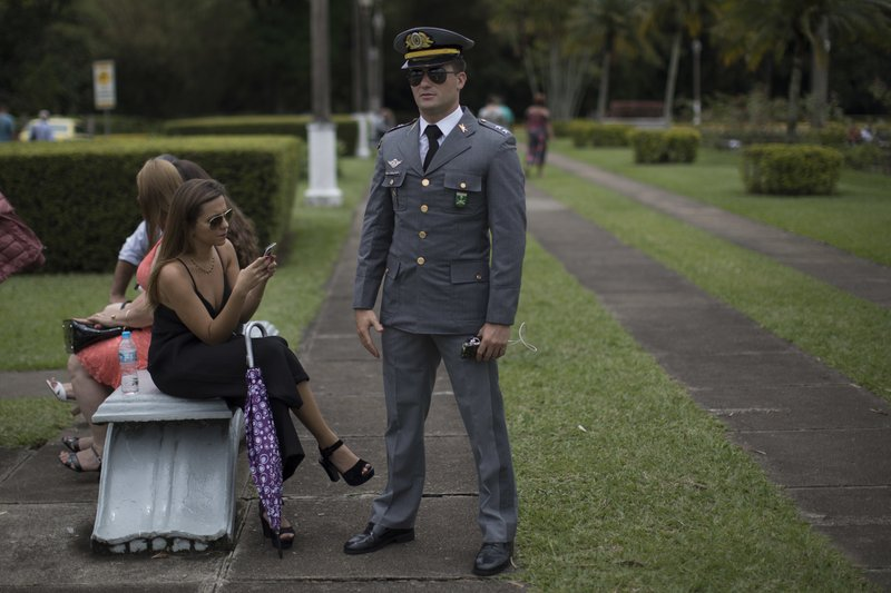 In this Dec. 1, 2018 photo, a Brazilian Army lieutenant stands in a garden after attending a graduation ceremony at the Agulhas Negras Military Academy, AMAN, in Resende, Brazil. (AP Photo/Leo Correa)