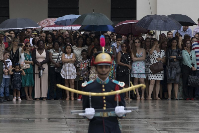 In this Dec. 1, 2018 photo, relatives and friends watch a cadet carry the saber of Duke Caxias, patron of the Brazilian Army, during a graduation ceremony at the Agulhas Negras Military Academy in Resende, Brazil. (AP Photo/Leo Correa)