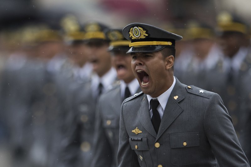 In this Dec. 1, 2018 photo, a Brazilian Army cadet sings while marching during his graduation ceremony at the Agulhas Negras Military Academy in Resende, Brazil. (AP Photo/Leo Correa)
