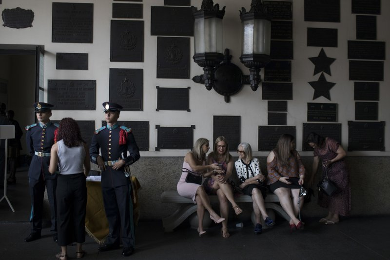 In this Dec. 1, 2018 photo, relatives and friends chat as they wait for the start of a graduation ceremony at the Agulhas Negras Military Academy in Resende, Brazil. (AP Photo/Leo Correa)