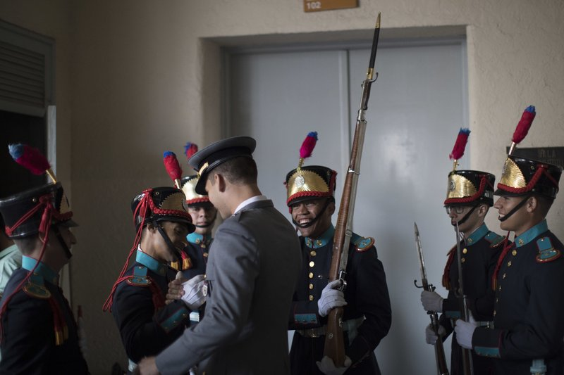 In this Dec. 1, 2018 photo, Brazilian Army cadets greet a colleague, back to the camera, before his graduation ceremony at the Agulhas Negras Military Academy in Resende, Brazil. (AP Photo/Leo Correa)